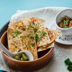 triangle slices of tortilla chips with spices and jalapeno in a brown bowl on a serving dish with a napkin and almond nuts on a blue background