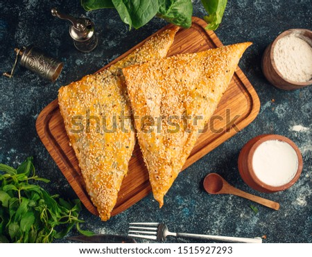 Triangled-shape bourekas baked pie with sesame seeds #1515927293