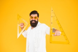 Triangles only have three sides. School teacher or university student smiling with geometric triangles for geometry lesson. Happy hipster holding triangles on yellow background. Lesson in triangles.