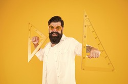 Triangles only have three sides. School teacher or university student smiling with geometric triangles for geometry lesson. Happy hipster holding triangles on yellow background. Lesson in triangles