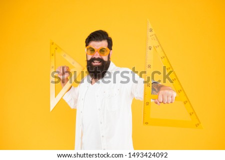 Triangles only have three sides. School teacher or university student smiling with geometric triangles for geometry lesson. Happy hipster holding triangles on yellow background. Lesson in triangles. #1493424092