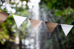 Triangular celebration paper flags with blurred bokeh background of trees and fountains. Selective focus.
