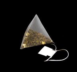 Triangular pyramid bag with green tea on a black background.