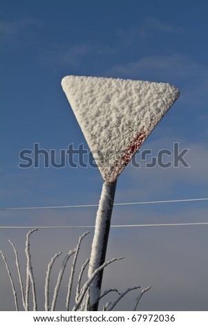 Triangular roadsign completely obscured by snow, on a sunny winters day.