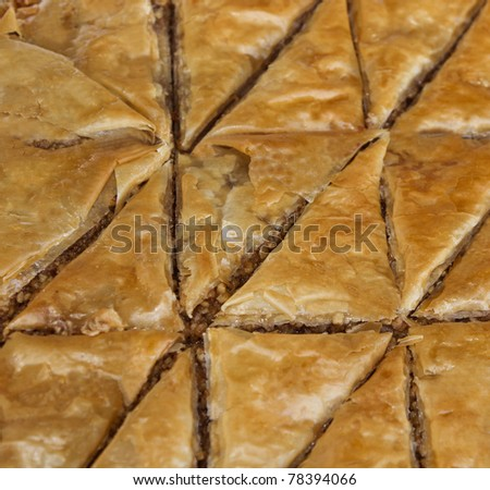 Triangular shapes of Baklava, a pastry made of ingredients including phyllo leaves, nuts, and honey.