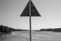 Triangular sign of river traffic from the back as well as the river and both banks in black and white.