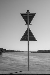 Triangular sign of river traffic from the back as well as the river itself in the background in black and white.