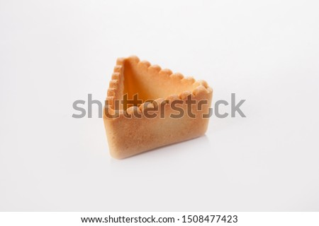 Triangular tartlet made of unleavened dough for filling with different fillings. The concept of cooking snacks. Photo on a white background. Isolated object. #1508477423