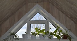 Triangular window with houseplants on the windowsill. Blue sky and trees view. Interior with wood trim
