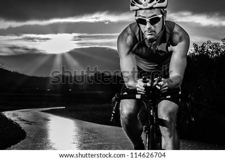 triathlete cycling in sunrise