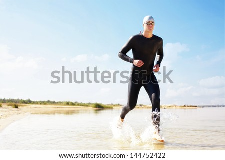 Triathlete running in to the water on triathlon race.