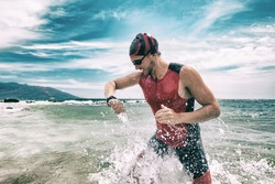 Triathlete swimmer looking at sport watch app using smartwatch during triathlon. Swimming man running out of ocean swim checking heart rate on smart watch. Professional athlete training for ironman.