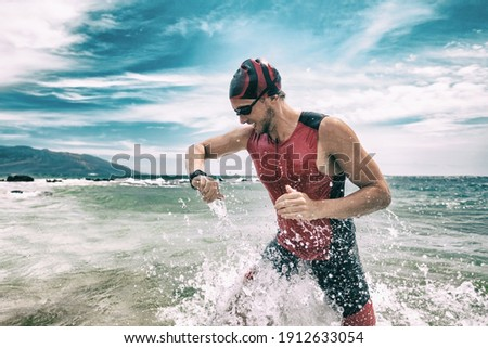 Triathlete swimmer looking at sport watch app using smartwatch during triathlon. Swimming man running out of ocean swim checking heart rate on smart watch. Professional athlete training for ironman. Stock foto ©