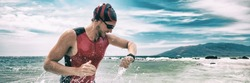Triathlon competition swimmer man swimming looking at heart rate monitor tracker smartwatch. Panoramic banner. Outdoor sports.