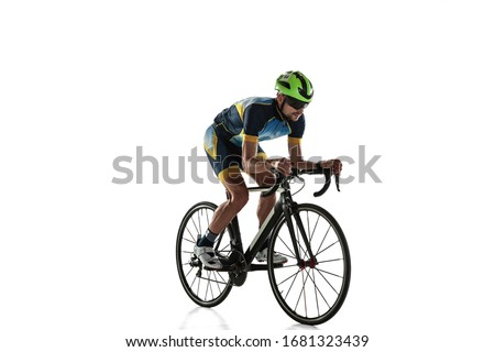 Triathlon male athlete cycle training isolated on white studio background. Caucasian fit triathlete practicing in cycling wearing sports equipment. Concept of healthy lifestyle, sport, action, motion. Foto stock ©