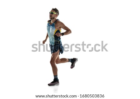 Triathlon male athlete running isolated on white studio background. Caucasian fit jogger, triathlete training wearing sports equipment. Concept of healthy lifestyle, sport, action, motion. In jump. Photo stock ©