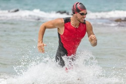 Triathlon swimming man. Male triathlete swimmer running out of ocean finishing swim race. Fit man ending swimming sprinting determined out of water in professional triathlon suit training for ironman.