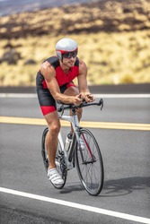Triathlon time trial cycling triathlete man wearing aero bike helmet with visor biking on competition race day riding road bicycle vertical shot.