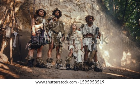 Tribe of Four Hunter-Gatherers Wearing Animal Skin Holding Stone Tipped Tools, Pose at the Entrance of their Cave. Portrait of Two Grown Male and Two Female Neanderthals and their Way of Living Stock photo ©