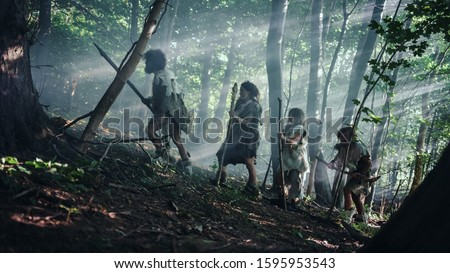 Tribe of Hunter-Gatherers Wearing Animal Skin Holding Stone Tipped Tools, Explore Prehistoric Forest in a Hunt for Animal Prey. Neanderthal Family Hunting in the Jungle or Migrating for Better Land Foto d'archivio ©