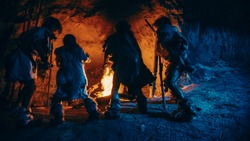 Tribe of Prehistoric Hunter-Gatherers Wearing Animal Skins Dance Around Bonfire Outside of Cave at Night. Neanderthal / Homo Sapiens Family Doing Pagan Religion Dancing Near Fire Back View Slow Motion