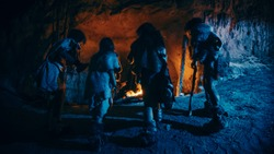 Tribe of Prehistoric Hunter-Gatherers Wearing Animal Skins Live in a Cave at Night. Neanderthal or Homo Sapiens Family Trying to Get Warm at the Bonfire, Holding Hands over Fire. Back View