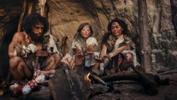 Tribe of Prehistoric Hunter-Gatherers Wearing Animal Skins Live in a Cave at Night. Neanderthal or Homo Sapiens Family Trying to Get Warm at the Bonfire, Holding Hands over Fire, Cooking Food