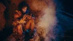 Tribe of Prehistoric, Primitive Hunter Gatherer Wearing Animal Skin Uses Smartphone in a Cave at Night. Neanderthal / Homo Sapiens Male Browsing Internet on Mobile Phone, Watches Videos