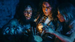 Tribe of Prehistoric, Primitive Hunter-Gatherers Wearing Animal Skins Use Smartphone in a Cave at Night. Neanderthal / Homo Sapiens Family Browsing Internet on Mobile Phone
