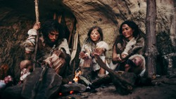 Tribe of Prehistoric PrimitiveHunter-Gatherers Wearing Animal Skins Live in a Cave at Night. Neanderthal or Homo Sapiens Family Trying to Get Warm at the Bonfire, Holding Hands over Fire, Cooking Food