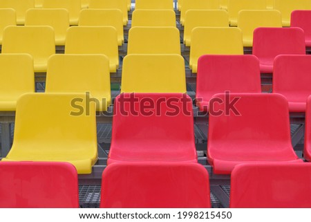 Tribune rows with diagonal yellow and red plastic seats. Concept of empty seats for fans in a sports stadium. Foto stock ©