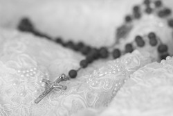 Tribute to Ansel Adams, artistic photo still life in black and white of embroidered fabric with nacre and rosary with crucifix