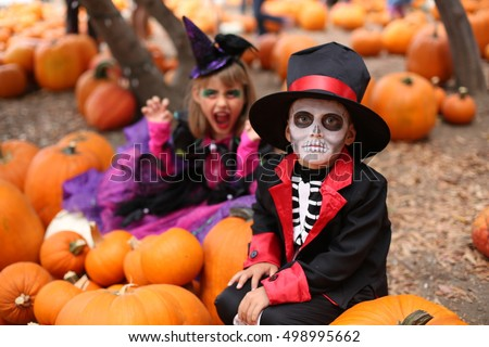 Trick or treat. Boy in a Halloween costume of skeleton with hat and smocking between orange pumpkins. Halloween kids with halloween costumes