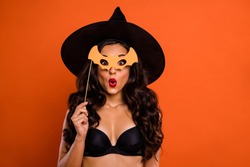 Trick or treat halloween concept photo of beautiful nude brunette charming lady holding bat shaped wooden stick see handsome wizard guy at party wear black witch cap isolated orange background