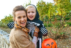 Trick or Treat. Portrait of smiling modern mother and daughter on Halloween outdoors