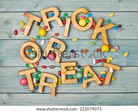 Trick or treat written with wooden letters and multiple candy sweets lying around over the covered with green boards surface composition