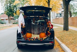 Trick or trunk. Black car trunk decorated for Halloween. Autumn fall decor with red pumpkins and yellow leaves for traditional October holiday outdoor. Social distance during coronavirus covid-19.