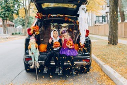 Trick or trunk. Children celebrating Halloween in trunk of car. Boy and girl with red pumpkins celebrating traditional October holiday outdoor. Social distance and safe alternative celebration.