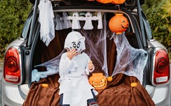 Trick or trunk. Trunk or treat. Happy child in ghost costume having fun celebrating Halloween party in decorated trunk of car. New trend and alternative safe outdoor celebration of traditional holiday