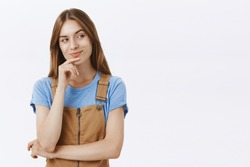 Tricky intelligent and creative good-looking female in overalls smirking gazing right with thoughtful curious look touching chin while thinking checking out cool guy with delighted smirk