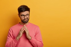 Tricky thoughtful bearded man steepls fingers, has some intention in mind, considers plans for future, looks aside mysteriously, has scheme, wears rosy sweater, isolated over yellow background