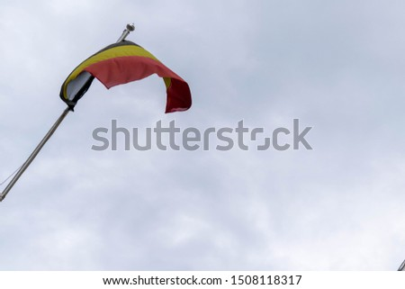 Tricolour Belgium National Flag blowing in the window on a flag pole. The three colours of the flag are black, yellow and red. Space for copy text. National pride background, EU parliament concept. #1508118317