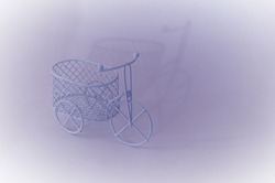 Tricycle vintage toy bike with expressive shadow. Magenta colors prevail. Bicycle day.