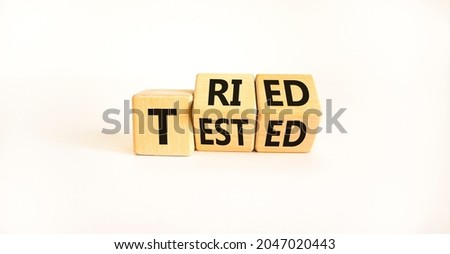 Tried and tested symbol. Turned wooden cubes and changed the concept word 'tried' to 'tested' on a beautiful white background. Copy space. Business and tried and tested concept. Foto stock ©