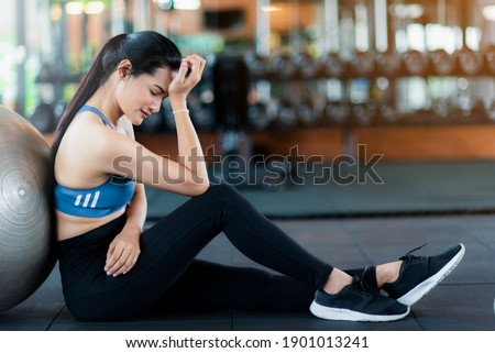 Tried asian woman is sitting on the floor after cardio workout. ストックフォト ©