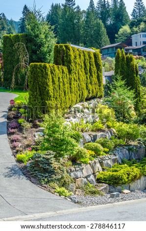 Trimmed bushes, flowers and stones in nicely decorated front yard of the house. Landscape design.