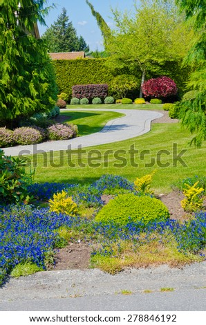 Trimmed bushes, flowers and stones in nicely decorated neighborhood. Landscape design.