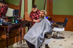 Trimming beard. Man client sit chair. Barbershop services. As gentleman and decent human being, you must tip your barber. Visit hairdresser. Maintaining shape. Hairdresser salon. Barbershop client.