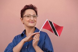 Trinidad and Tobago flag. Woman holding Trinidad and Tobago flag. Nice portrait of happy middle aged lady 40 50 years old with a national flag over pink wall background on the street outdoors.