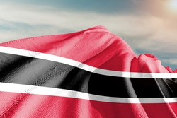 Trinidad and Tobago national flag cloth fabric waving on beautiful sky.